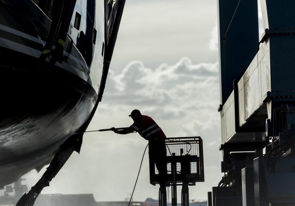 man power washing a vessel during marina berthing
